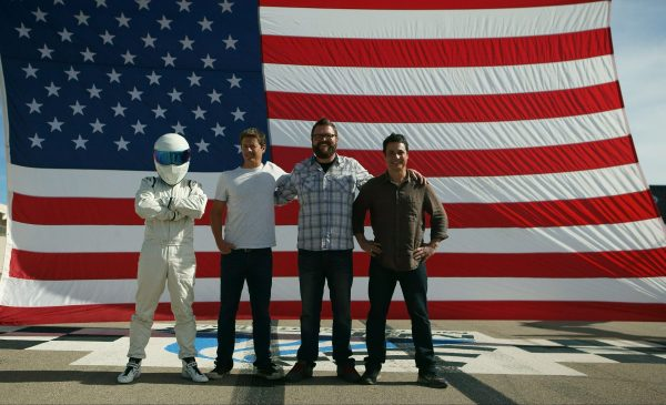 Picture Shows: Tanner Foust, Rutledge Wood, and Adam Ferrara with Stig in front of American Flag